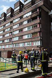 London, UK. 4th May, 2018. London Fire Brigade firefighters attend to a fire in a flat on the fourth floor of a block in Windlass Place, Surrey Quays. London Fire Brigade's press liaison officer advised that a total of eight pumps were called out and that no one was present in the flat at the time of the fire.