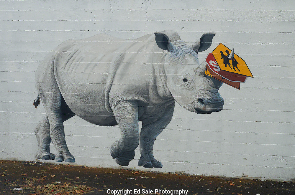 A painted wall mural in Portland, Oregon, depicts a white Rinoceros with a stop sign and a cross-walk warning sign pierced by it's horn.