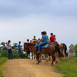 Gettysburg, PA, USA - June 20, 2018: A group takes a horseback tour of the battlefield, stopping at the General Sickles marker, showing where he was wounded on the second day of fighting.