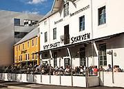 Vertshuset Scarven pub with people drinking in summer sunshine outdoors, Tromso, Norway
