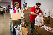 05 NOVEMBER 2013 - PHOENIX, AZ: KENYON CASPER, left, and PAUL BYLINOWSKI, volunteers at St. Mary's Food Bank in Phoenix, AZ, pack carts for clients. Demand at St. Mary's has continued to increase even as government assistance is reduced. Over the summer, St. Mary's Phoenix location provided emergency food for 300 - 400 families per day. They are currently supporting about 600 families per day. Part of the increase is seasonal but a large part of it is no clients coming to the food bank for the first time. More than 1.1 million Arizonans who use the Supplemental Nutrition Assistance Program, known as food stamps, saw their benefits reduced Friday, Nov. 1, in a long-planned national cut that was tied to the economic stimulus which was a part of the American Recovery and Reinvestment Act. The cuts imposed last week range from $11 a month for a single recipient to $65 or more for large families. Many of SNAP receipients already use food banks to supplement their government assistance and the cuts in the SNAP program are expected to increase demand even more.   PHOTO BY JACK KURTZ