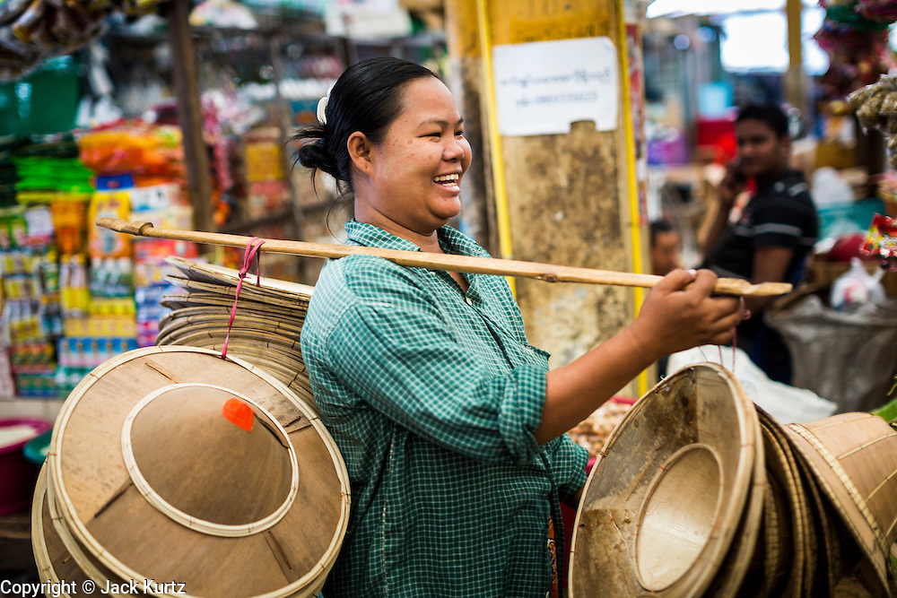 23 MAY 2013 - MAE SOT, TAK, THAILAND: A Burmese woman sells traditional Burmese conical hats in the Burmese market in Mae Sot, Thailand. Fifty years of political turmoil in Burma (Myanmar) has led millions of Burmese to leave their country. Many have settled in neighboring Thailand. Mae Sot, on the Mae Nam Moei (Moei River) is the center of the Burmese emigre community in central western Thailand. There are hundreds of thousands of Burmese refugees and migrants in the area. Many live a shadowy existence without papers and without recourse if they cross Thai authorities. The Burmese have their own schools and hospitals (with funding provided by NGOs). Burmese restaurants and tea houses are common in the area.    PHOTO BY JACK KURTZ