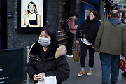 On the day that the UK Governments Chief Scientific Advisor, Sir Patrick Vallance said that the Coronavirus Covid-19 outbreak was now spreading person to person in the UK, a member of the Chinese community wears a surgical mask outside the London Palladium near Chinatown in the West End, on 6th March 2020, in London, England.