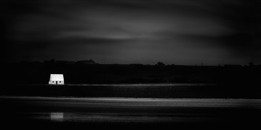 The White House lit up on a dark night and reflecting in the stream at St Ouen's Bay, Jersey, Channel Islands