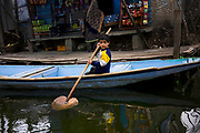 A child tries to ride a boat with a bow, while his mother is shopping in a small shop.<br /> There are several shops which cater their daily needs. they don&#39;t have to go to<br /> mainland to buy things, but the mode of transport is Boat. © Sandipa Malakar