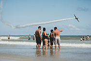 Spectators enjoy the 2014 Wings and Waves Air Show in Daytona Beach, Florida on October 12, 2014. A 1953 NORTH AMERICAN MEDORE T-6G, a fixed-wing single engine plane, is seen in the air.