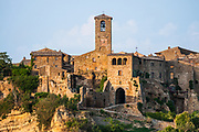 """A view of the village of Civita di Bagnoregio.<br /> Civita di Bagnoregio is a town in the Province of Viterbo in central Italy, a suburb of the comune of Bagnoregio, 1 kilometre (0.6 mi) east from it. It is about 120 kilometres (75 mi) north of Rome. Civita was founded by Etruscans more than 2,500 years ago. Bagnoregio continues as a small but prosperous town, while Civita became known in Italian as La città che muore (""""The Dying Town""""). Civita has only recently been experiencing a tourist revival. The population today varies from about 7 people in winter to more than 100 in summer.The town was placed on the World Monuments Fund's 2006 Watch List of the 100 Most Endangered Sites, because of threats it faces from erosion and unregulated tourism."""