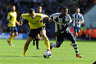 West Brom's Stephane Sessegnon ® is held by Sunderland's  Adam Johnson. Barclays Premier league match, West Bromwich Albion v Sunderland at the Hawthorns in West Bromwich, England on Sat 21st Sept 2013. pic by Andrew Orchard, Andrew Orchard sports photography,