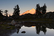 Mount Baker, a 10,781 foot (3,286 meter) volcano located in Whatcom County, Washington state, is partially reflected in a mountain tarn near Artist Point in the North Cascades. Mount Baker, which is part of the Cascade Range of mountains, has the second-most thermally active crater in the range, second only to Mount St. Helens. Baker's volcanic cone is relatively young, possibly less than 100,000 years old, even though the area where it sits has been volcanically active for 1.5 million years.