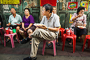 11 SEPTEMBER 2013 - BANGKOK, THAILAND:  A man sits on a stool and eats curry at a curry stand in the Chinatown section of Bangkok. Thailand in general, and Bangkok in particular, has a vibrant tradition of street food and eating on the run. In recent years, Bangkok's street food has become something of an international landmark and is being written about in glossy travel magazines and in the pages of the New York Times.        PHOTO BY JACK KURTZ