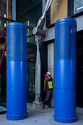 Construction worker smokes under blue theme coloured pillars and struts on development opposite Tate Modern gallery on London's Southbank.