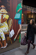 Construction hoarding for forthcoming Kate Spade in Regent Street, central London. A woman shopper walks beneath the illustration of women outside a cafe, wearing the clothing of this fashion brand. Kate Spade New York is an American fashion design house founded as Kate Spade Handbags in January 1993, by Kate Spade. The name is rendered on products (and occasionally in literature) in all lowercase (kate spade). Jack Spade is the name for the Kate Spade brand's line for men.