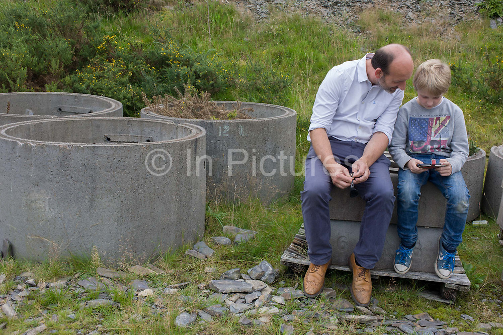 A father and son look at a smartphone together during a day out in wales, sit on concrete blocks. The boy's device is being shown to the father so he can better understand its functions and features, something that the older generation can't always comprehend. They sit on concrete building materials, circular pipes a local building project.