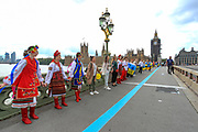 Members of the Ukrainian community in Britain created a human chain on Westminster Bridge, outside Westminster Palace, Houses of Parliament to mark the anniversary of Ukraine's national Flag in central London on Sunday, Aug 22, 2021. (VX Photo/ Vudi Xhymshiti)