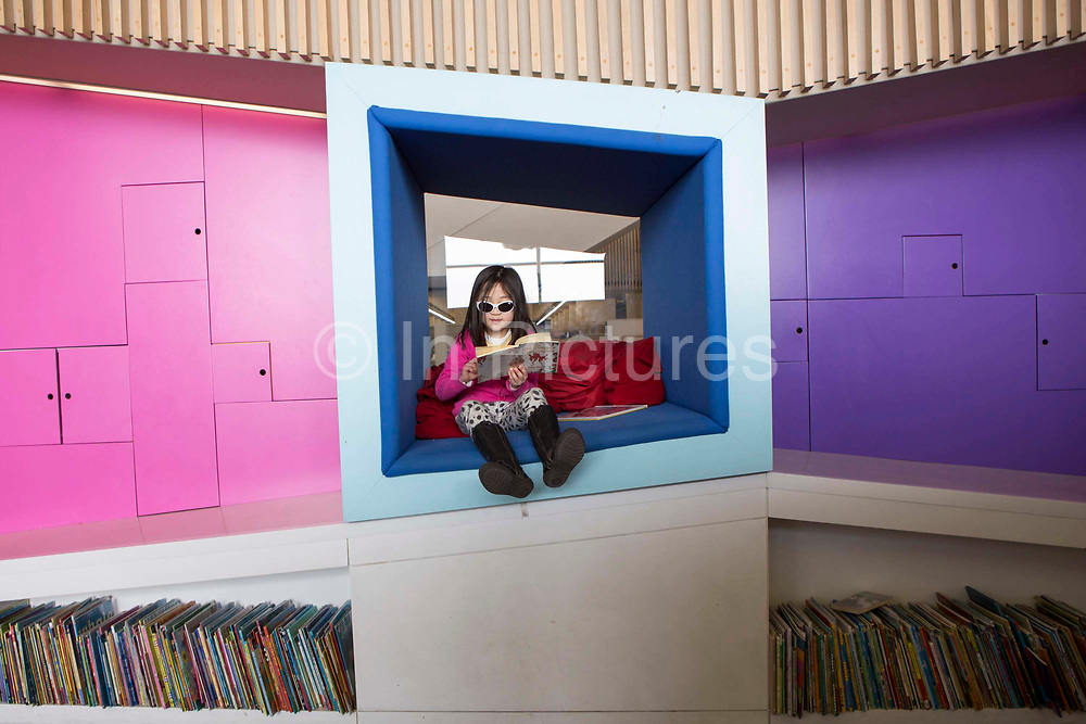 A young girl reading inside the library of the Hive in Worcester, UK. The first fully integrated university and public library in the UK.