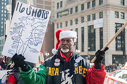 "© Licensed to London News Pictures. 24/12/2015. Chicago, USA. Hundreds of people gather to march down Michigan Avenue's ""Magnificent Mile"" shopping district on Christmas Eve to protest against the alleged police cover up related to the fatal shooting of Laquand McDonald by a Chicago policeman.  Flanked by members of the Chicago police force, protestors were chanting ""16 shots and a cover up,"" and calling for Chicago Mayor Rahm Emanuel to resign, on what was described as ""Black Christmas"".  Photo credit : Stephen Chung/LNP"