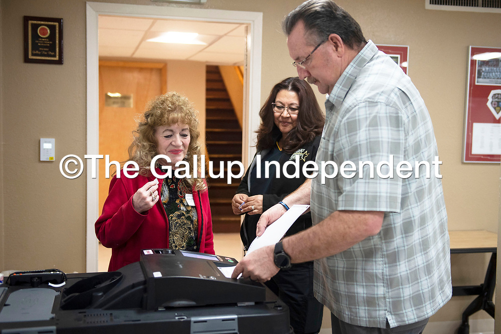 Mary Ann Tafoya, left, an election clerk and Judith Goins, center, watch John Goins submit his ballot at the Southside Fire Station No. 1 Tuesday, March 3 for the 2020 Municipal Officer Election in Gallup.
