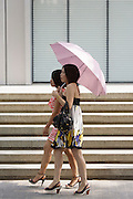 Ladies walking with umbrellas in a Shanghai street.