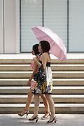 Ladies walking with umbrellas in a Shanghai street.