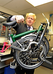 © licensed to London News Pictures. LONDON, UK.  02/06/11. Boris Johnson holds up a Brompton Folding Bicycle. The Mayor of London Boris Johnson visits two major manufacturing firms today, 02 June 2011, to see the role they play in supporting London's economy and why the UK's capital city  is so critical to their continued success. He called in to Fuller's in Chiswick, London's only traditional family brewery, to see their new multi-million pound brewing facility. He went on to visit Brompton bike factory. Where he met Brompton inventor Andrew Ritchie, who still owns the famous company and remains its Technical Director.  Photo credit should read Stephen Simpson/LNP