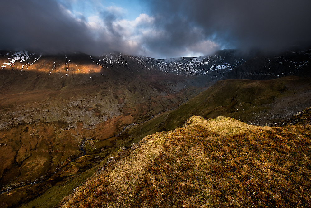 Standing on a buttress high above Cwm Llachar in the Carneddau mountains of Snowdonia, even the patches of sunshine brought little relief from the bitter cold. The ascent to the dark cloud-shackled summit of Carnedd Dafydd was steep, ominous and icy, so in failing evening light we drank a last hot coffee and began our descent in gathering cold dusk