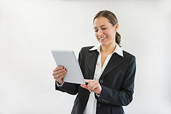 Businesswoman in black suit using digital tablet, smiling
