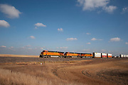 Railroad train pulling hundreds of containers laden with goods being transported across the North Dakota prarie, easing its way powerfully through the prarie landscape under a blue clouded sky near Minot, North Dakota, United States. Some of these trains can be up to a mile long.