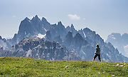"A hiker admires sharp peaks of the Cadini Group in the Sesto Dolomites, Italy, Europe. In the Cadini di Misurina, Cima Grande rises to 2999 meters (9839 feet), between Cima Piccola and Cima Ovest. The Cadini Group is in the Sesto Dolomites (Dolomiti di Sesto, or Sexten/Sextner/Sextener Dolomiten) which lie north of the Fiume Ansiei valley, in the municipality of Auronzo. From the Rifugio Auronzo toll road, hike for spectacular views around Tre Cime di Lavaredo (Italian for ""Three Peaks of Lavaredo,"" called Drei Zinnen or ""Three Merlons"" in German). The Dolomites are part of the Southern Limestone Alps. UNESCO honored the Dolomites as a natural World Heritage Site in 2009."