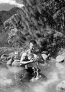 Photographie d'un pompier torse nu se baignant dans une rivière. Prise de vue en Noir et blanc.