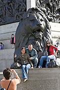 Tourists pose for photographs on lion statue at base of Nelson's Column, Trafalgar Square, London, UK