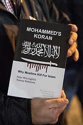 """© Licensed to London News Pictures . 03/11/2017 . Manchester , UK . A man holds up a copy of Mohammed's Koran by Peter McLoughlin and Tommy Robinson . Hundreds of fans of Tommy Robinson (real name Stephen Yaxley-Lennon ) queue up for books at the launch of the former EDL leader's book """" Mohammed's Koran """" at Castlefield Bowl . Originally planned as a ticket-only event at Bowlers Exhibition Centre , the launch was moved at short notice to a public location in the city . Photo credit : Joel Goodman/LNP"""