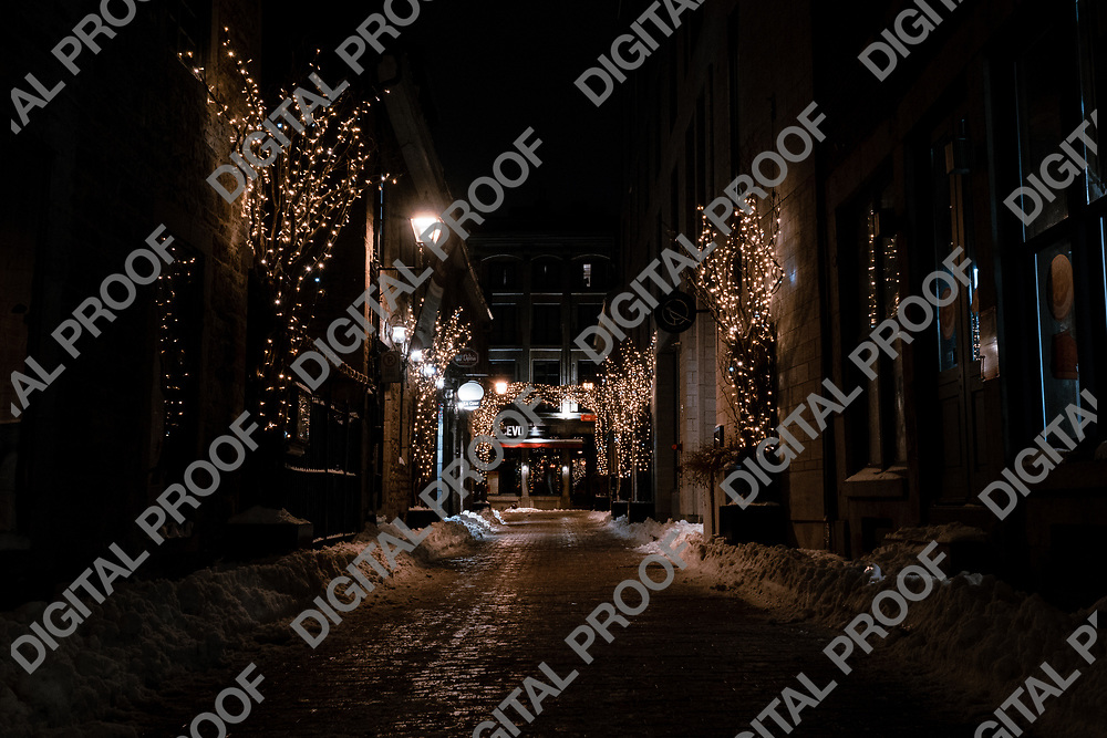 Montreal, Quebec, Canada - January 3, 2021 Rue Saint Amable during winter night with christmas lights and snow without people viewed from Place Jacques-Cartier in Montreal Old Port