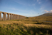Ribblehead Viaduct or Batty Moss Viaduct carries the Settle-Carlisle Railway across valley of the River Ribble at Ribblehead, in North Yorkshire Dales, England, UK. This impressive Victorian architectural wonder was designed by engineer, John Sydney Crossley and was built between 1870 and 1874. To the right is Ingleborough, the second highest mountain in the Yorkshire Dales, at 723 metres. It is one of the Yorkshire Three Peaks.