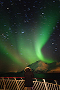 A figure stands on a boat watching the Aurora Borealis, the Northern Lights, in northern Norway