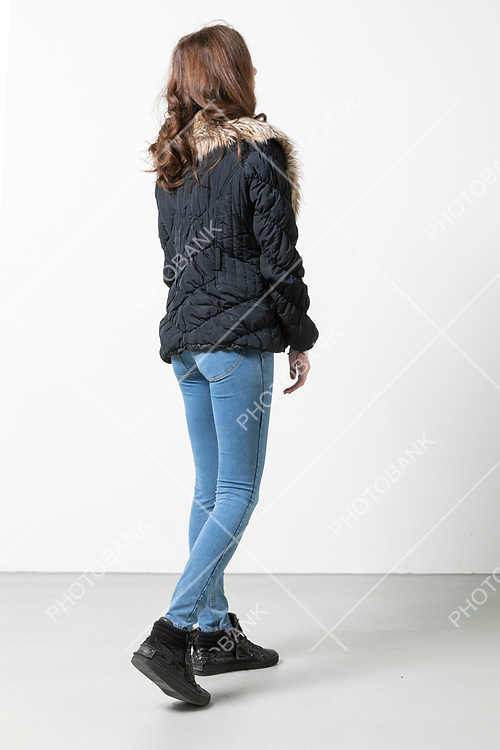 Woman with jacket and long hair walks and is seen from behind, the background is white