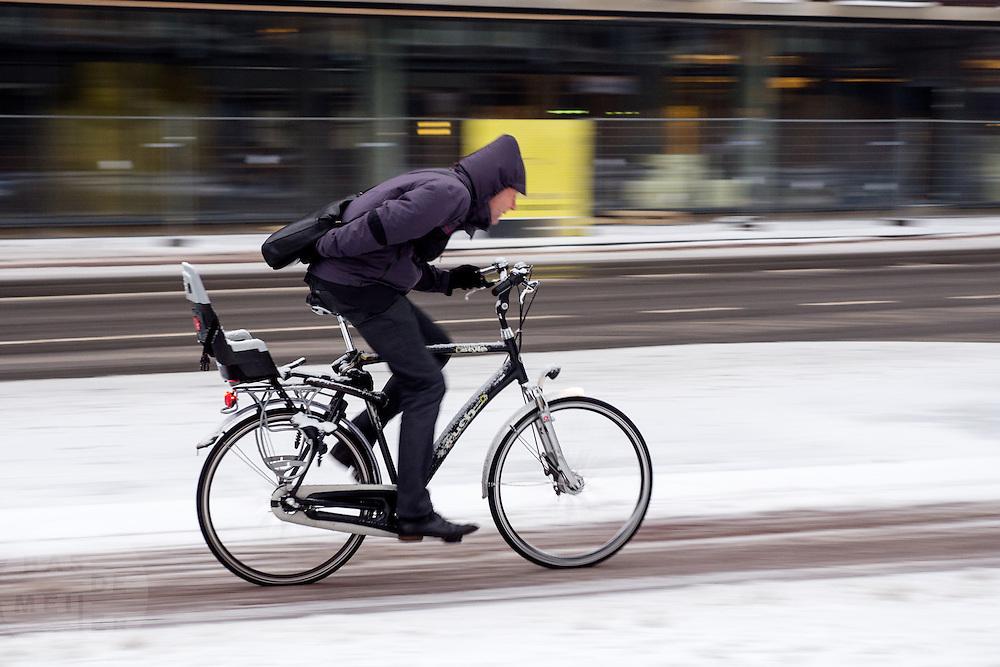 Een forens in Utrecht ploetert door de koude tegenwind over een besneeuwd fietspad. De sneeuwval in het westen van land heeft de nodige overlast veroorzaakt.