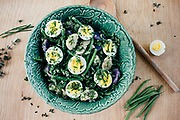 French style potato salad with green beans and hard boiled eggs served in a green bowl from Portugal on wood surface.