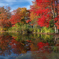 Brilliant New England fall foliage peak colors at Factory Pond in Holliston, Massachusetts. This Massachusetts autumn photography image was inspired by the red glorious fall colors and pond reflection. The photograph was taken at the site where the Darling Woolen Mill stood. The mill was lost to a ire in 1933. <br />