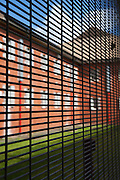 Looking through a security fence at one of the wings of the prison. HMP The Mount, Bovingdon, Hertfordshire
