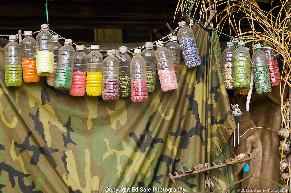 Colorful water bottles filled with beads hang from a porch in Locke, California