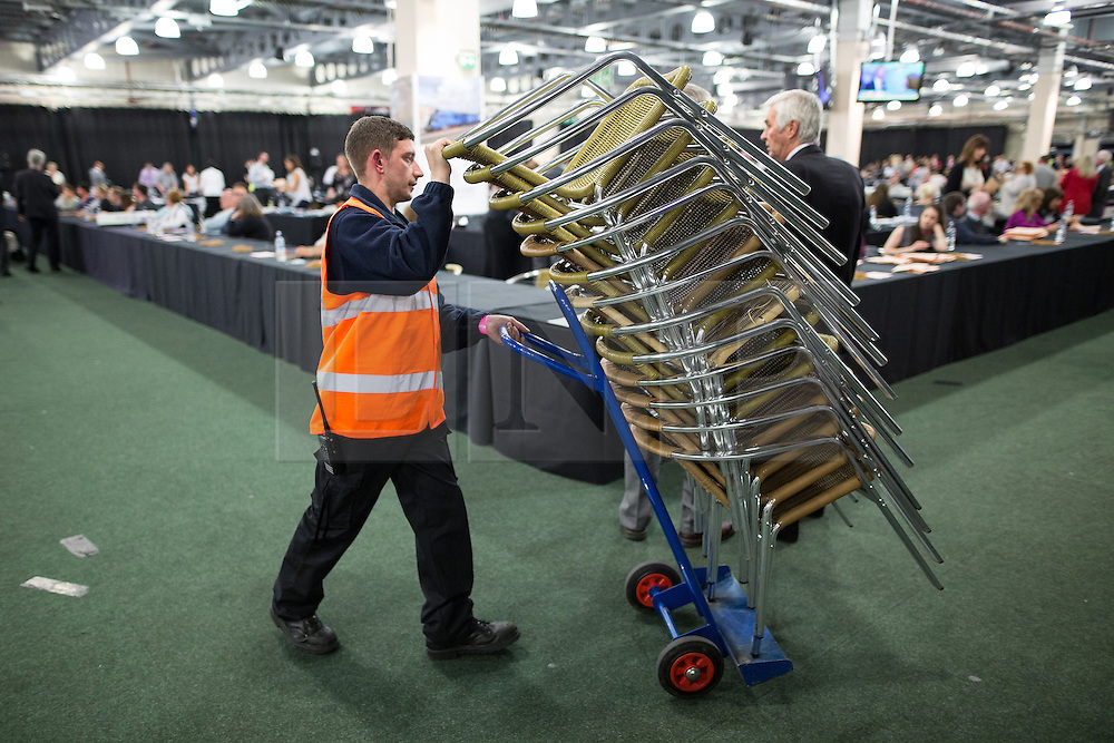 © Licensed to London News Pictures . 07/05/2015 . Doncaster , UK . A man wheels chairs across the counting hall . The count for the 2015 General Election in Labour Party leader Ed Miliband's constituency of Doncaster North , at Doncaster Racecourse . Photo credit : Joel Goodman/LNP