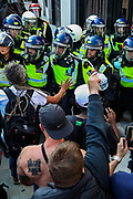 "A protestor throws water next to police officers during a ""Resist and Act for Freedom"" protest against a mandatory coronavirus vaccine, wearing masks, social distancing and a second lockdown, nearby Canada House in Trafalgar Square, London on Saturday, Sept. 19, 2020. (VXP Photo/ Vudi Xhymshiti)"