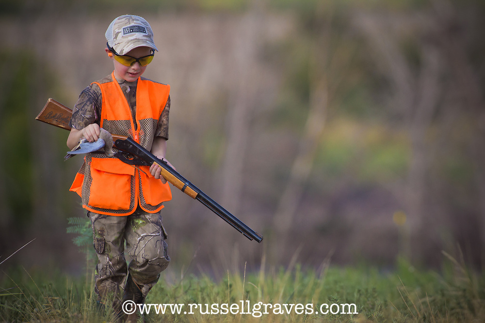 YOUNG BIY WEARING BLAZE ORANGE AND HOLDING A RED RIDER BB GUN CARRYING A HARVESTED DOVE
