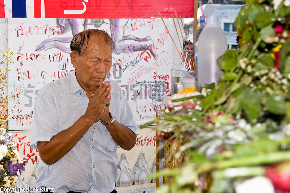 Apr. 14 - Bangkok, Thailand: A man prays and pays respects at the coffins of Red Shirts who died in street fighting Saturday. The bodies of the Red Shirts who died during Saturday's fighting are lying in repose at Democracy Monument. Thousands of Thais have filed past to show their respect. The Red Shirts moved their main protest its original location in the old part of Bangkok to the Ratchaprasong intersection, in the center of Bangkok's shopping malls and five star hotels. Many signs of last weekend's violence is still on display around their original encampment though. Photo by Jack Kurtz