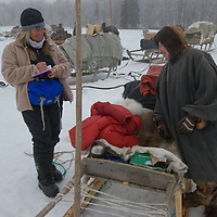"""North of the Arctic Circle in Russia, writer Gretel Ehrlich laughs with Katerina (""""Katya"""") Vaucheskaya, a member of the last nomadic Komi reindeer herding clan, who is wearing a traditional malitsa robe as she loads her sled to migrate to another camp."""
