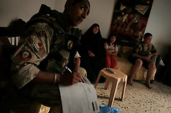 An Iraqi soldier fills out a family census form  in the Baghdad Sunni neighborhood of Ghazaliyah. The census - part of an operation by bolstered US and Iraqi forces in the hopes of getting a handle on the extraordinary numbers of sectarian killings in Baghdad - was carried out by the recently extended Alaska-based 4BN 23rd Infantry Regiment of the 172nd Stryker Brigade - Baghdad, Iraq on Tuesday August 15, 2006. The brigade, which was in the process of rotating home at the end of a year tour in Mosul and northwestern Iraq, was diverted to the capital for an undetermined number of additional months.