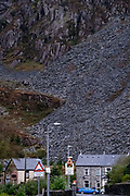 A mountain of slate dominates terraced housing, on 3rd October 2021, in Blaenau Ffestiniog, Gwynedd, Wales. The derelict slate mines around Blaenau Ffestiniog in north Wales were awarded UNESCO World Heritage status in 2021. The industry's heyday was the 1890s when the Welsh slate industry employed approximately 17,000 workers, producing almost 500,000 tonnes of slate a year, around a third of all roofing slate used in the world in the late 19th century. Only 10% of slate was ever of good enough quality and the surrounding mountains now have slate waste and the ruined remains of machinery, workshops and shelters have changed the landscape for square miles.