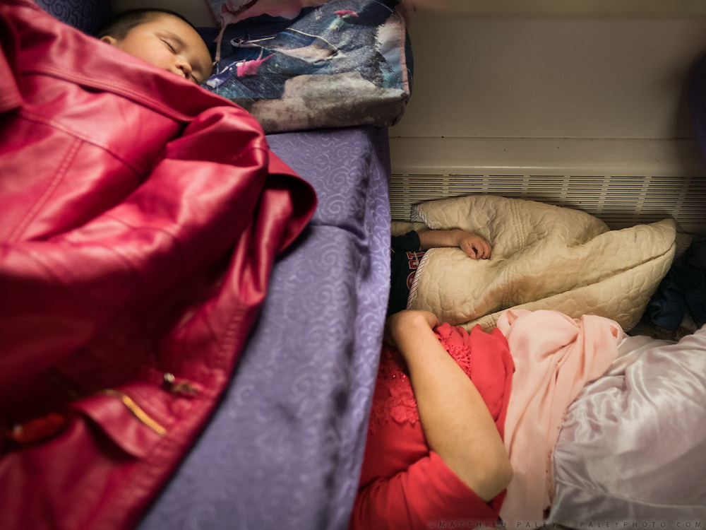 A uighur family on the long trip from Xian to Urumchi (over 40 hours) is in the hard sleeper section. The mother sleeps on the floor with the youngster while his brother sleeps on the seats. Life in the seating wagons in the train from Hong Kong to Urumqi, Xinjiang.