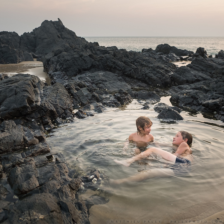 Two brothers talk and spend a quiet time in a natural pool in the ocean.