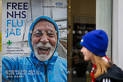 © Licensed to London News Pictures. 26/10/2021. London, UK. A woman walks past a 'Free NHS Flu Jab' poster displayed in Boots pharmacy in Wood Green, north London. People are being urged to get their flu jab ahead of the winter as figures from the drug maker Reckitt suggest that the cold and flu season will be worse this year than normal. Health Secretary Sajid Javid is considering making flu jabs mandatory for all NHS staff.   Photo credit: Dinendra Haria/LNP
